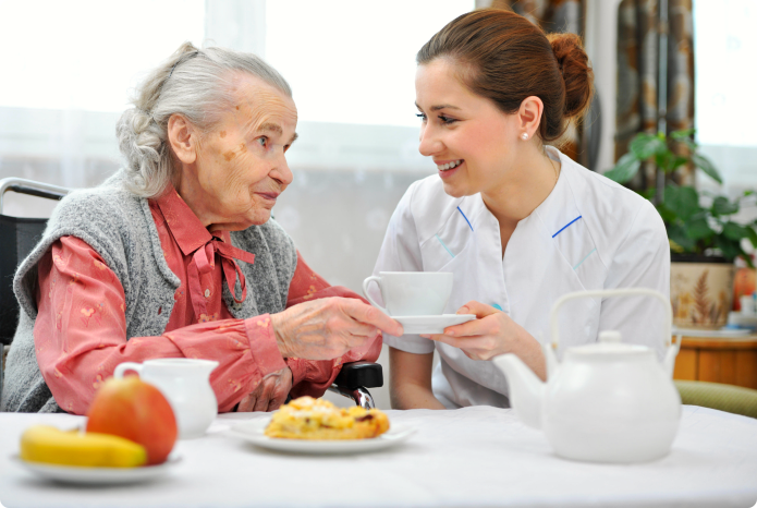 caregiver helping her patient in eating